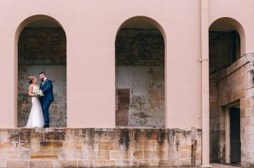 newly-wed-standing-beside-white-concrete-building-3156667 (1)